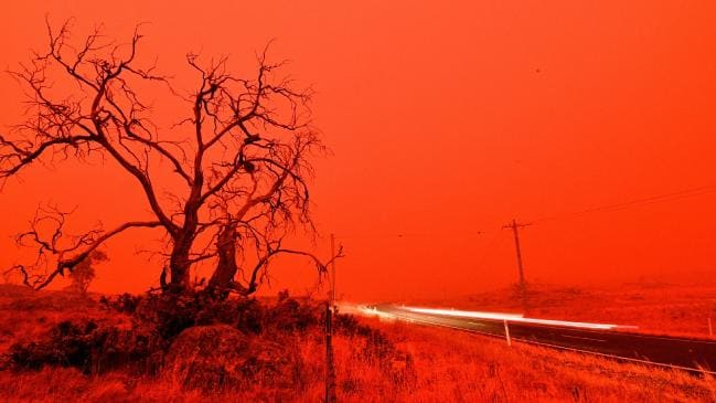 A long exposure picture shows a car commuting on a road as the sky turns red from smoke of the Snowy Valley bushfire on the outskirts of Cooma on Saturday. Picture: Saeed Khan / AFPSource:AFP